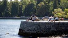 People sit along the Stanley Park seawall in Vancouver on Aug. 25, 2013. (Darryl Dyck/The Canadian Press)