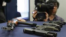 Weapons seized during several gang-related arrests are displayed during a police news conference in Vancouver, B.C., on March 6, 2009. A new study from Justice Canada says gun-related violent crime may be costing Canadians more than $3 billion a year. (Darryl Dyck/The Canadian Press)