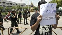 A Thai student holds an anti-coup sign in front of a group of soldiers during a brief protest near the Democracy Monument in Bangkok, Thailand Friday, May 23, 2014. (Apichart Weerawong/AP)