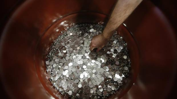 An employee reaches into a drum of rejected nickel plated blanks roll along a conveyor belt at the Royal Canadian Mint in Winnipeg Tuesday, April 4, 2017.