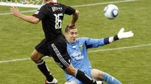DC United forward Josh Wolff. left, watches as his shot goes over the outstretched arm of Portland Timbers goalkeeper Troy Perkins on the way to the goal during the second half of their MLS soccer game in Portland, Ore., Sunday, May, 29, 2011. (Don Ryan/AP)