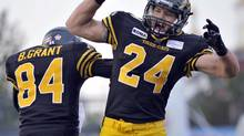 Hamilton Tiger-Cats' Daryl Stephenson, right, celebrates his touchdown with teammate Bakari Grant against the Montreal Alouettes during CFL football action in Hamilton, Ont., on July 21, 2012. (J.P. MOCZULSKI/THE CANADIAN PRESS)