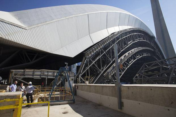 Dave McCormick, engineering manager at the Rogers Centre, left, speaks with Globe reporter Rob MacLeod and a worker, in front of a fully opened roof, in Toronto on Wednesday, June 24, 2015.