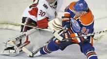 Edmonton Oilers' Mike Comrie (R) is hauled down from behind on a breakaway against Ottawa Senators goalie Brian Elliott during the first period of their NHL hockey game in Edmonton March 9, 2010. REUTERS/Dan Riedlhuber (DAN RIEDLHUBER)