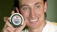 Wayne Gretzky holds up his record-breaking puck after breaking Gordie Howe's lifetime point record in Edmonton on Oct. 15, 1989. (The Canadian Press)