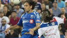 Olympique Lyonnais' Bafetimbi Gomis looks on as Montreal Impact's Alessandro Nesta heads the ball clear during the first half of an international friendly match at Saputo Stadium in Montreal on Tuesday, July 24, 2012. (Peter Mccabe/THE CANADIAN PRESS)