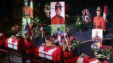 The caskets of Const. Dave Joseph Ross, 32, from Victoriaville, Que., left to right, Const. Douglas James Larche, 40, from Saint John, N.B. and Const. Fabrice Georges Gevaudan, 45, from Boulogne-Billancourt, France, sit in Wesleyan Celebration Centre during the public visitation in Moncton, N.B. on Monday, June 9, 2014. A regimental funeral will take place Tuesday for the three RCMP officers who were slain in Moncton last week.