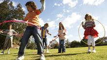 Children play with hula hoops. (Bec Parsons/Getty Images)