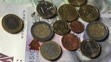 Euro coins and Slovak crown banknotes are seen in Bratislava on January 5, 2009. (SAMUEL KUBANI/AFP/Getty Images)