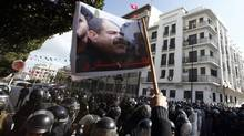 Tunisian protesters shout slogans during a demonstration after the death of Tunisian opposition leader Chokri Belaid (pictured on flag), outside the Interior ministry in Tunis February 6, 2013. (ANIS MILI/REUTERS)