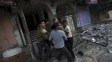 Palestinians carry an injured man Monday after an Israeli strike on a building in Gaza City. It was the second time the building was hit in two days. (Bernat Armangue/Associated Press)