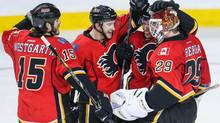 Calgary Flames players congratulate Flames goalie Reto Berra (29) after their overtime win over Nashville Predators at Scotiabank Saddledome. (Sergei Belski/USA Today Sports)