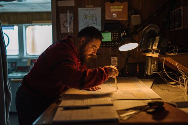 On the bridge, first mate Jim Pierce of Nova Scotia studies a map of eastern Lake Ontario.