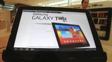 A woman walks near Samsung Electronics' new tablet Galaxy Tab 10.1 which features the 10.1-inch touch screen and runs on Android 3.1 during its unveiling ceremony in Seoul, South Korea, Wednesday, July 20, 2011. (Lee Jin-man/AP)