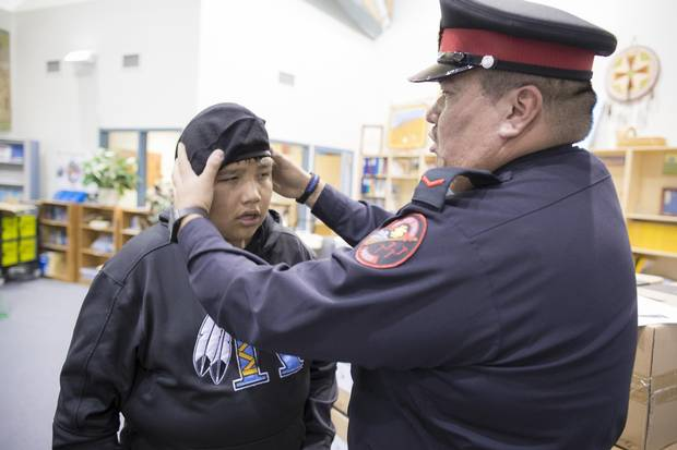 Senior Constable Brice Iron Shirt, the school resource officer in Stand Off, Alta., helps fit a new hat on student cadet, Felix Many Bears. The local police department has a student recruitment program for teens who can join the cadet program to learn about local policing and community concerns.