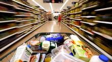 A customer pushes a grocery cart through the food aisles at a Sainsbury's supermarket, in London Colney, U.K., on Friday, Feb. 29, 2008. (CHRIS RATCLIFFE)