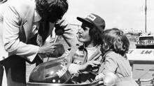 A 1974 photo shows Gilles Villeneuve being interviewed in his car as his son Jacques stands by. (AFP/AFP)