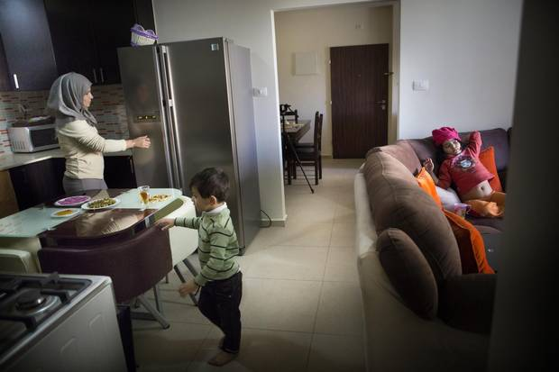Ms. Salameh with the children at the new condo in Rawabi.