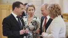 Russia's new President Vladimir Putin (2nd R), his wife Lyudmila, former President Dmitry Medvedev (L) and his wife Svetlana speak during a reception dedicated to the start of Putin's term at the Kremlin in Moscow, May 7, 2012. (RIA NOVOSTI/REUTERS)