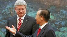 Canada's Prime Minister Stephen Harper looks on as Chinese Premier Wen Jiabao gestures after a signing ceremony at the Great Hall of the People in Beijing Feb. 8, 2012. (Diego Azubel/Reuters/Pool/Diego Azubel/Reuters/Pool)