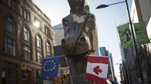 A giant Trojan horse statue holding EU and Canadian flags in its mouth, set up by the social activist group 'Council of Canadians' in front of the Ontario Investment and Trade Centre in Toronto to protest the Comprehensive Economic and Trade Agreement (CETA) between Canada and the European Union. (MARK BLINCH/REUTERS)