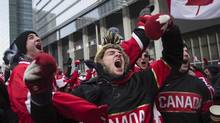 Hockey fans celebrate in Toronto's Maple Leaf Square during Canada's gold-medal Olympic men's hockey win on Sunday, February 23, 2014. Canada beat Sweden 3-0 to win the gold medal. (Chris Young/THE CANADIAN PRESS)