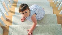 A baby crawls up the stairs, taking baby steps. (Thinkstock/Photos.com)