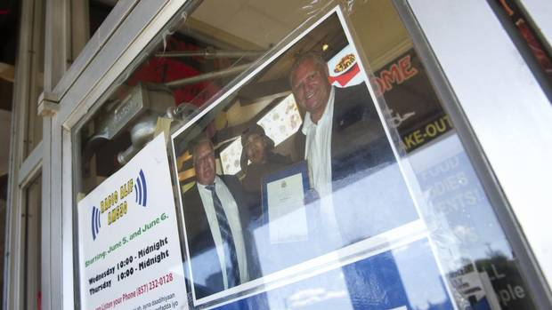 A photo of the owner of Istar Restaurant, Istarlin Mohamed, with Mayor Rob Ford and Councillor Doug Ford is posted on the door at her restaurant in Toronto, Ont., June 3, 2013. (Kevin Van Paassen/The Globe and Mail)
