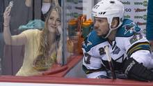 A fan takes a photo on her cellphone with San Jose Sharks Scott Hannan while the Sharks played the Vancouver Canucks during the third period of game 2 of the Stanley Cup playoffs in Vancouver May 3, 2013. (John Lehmann/The Globe and Mail)