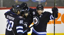 Winnipeg Jets' Andrew Ladd (R) celebrates his goal against the Tampa Bay Lightning with Nik Antropov (L) and Johnny Oduya during the second period of their NHL game in Winnipeg, November 14, 2011. (FRED GREENSLADE)