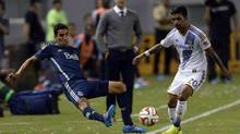 Vancouver Whitecaps midfielder Mehdi Ballouchy (8) attempts to keep the ball inbounds defended by Los Angeles Galaxy defender A.J. DeLaGarza (20) during the first half at StubHub Center in Los Angeles on Aug. 23. (Kelvin Kuo/USA Today Sports)