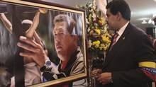 Acting Venezuelan President Nicolas Maduro, right, looks at a photograph of late Venezuelan President Hugo Chavez during the funeral at the military academy in Caracas on March 8, 2013. Venezuela has set an election date of April 14, with Mr. Maduro seen as the early favourite. (REUTERS)