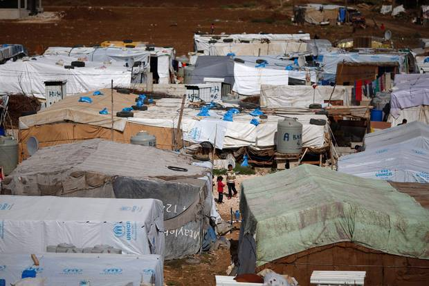 Syrian refugees stand outside their tents at a Syrian refugee camp in the town of Hosh Hareem, in the Bekaa valley, east Lebanon, Wednesday, Oct. 28, 2015.