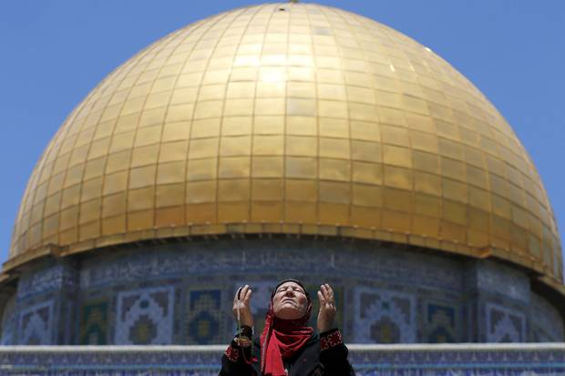 June 19, 2015: A Palestinian woman prays in front of the Dome of the Rock on the first Friday of the holy month of Ramadan at the Jerusalem compound known to Muslims as the Noble Sanctuary and to Jews as the Temple Mount.