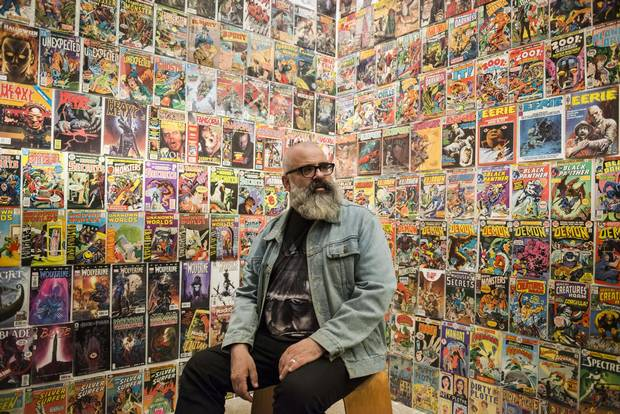 Exhibition curator Jim Shedden poses against a wall displaying hundreds of influential comic books.