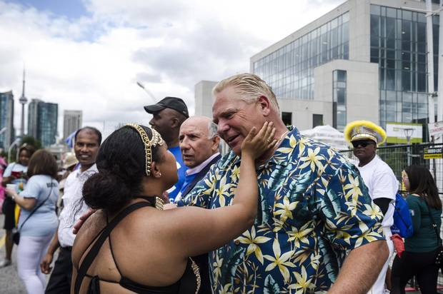 A parade participant greets Doug Ford during the Grand Parade at the Caribbean Carnival in Toronto in August.