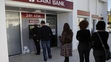 People queue to use an ATM machine outside of a Laiki Bank branch in Larnaca, Cyprus, on March 16, 2013. Many rushed to cooperative banks which are open Saturdays in Cyprus after learning that the terms of a bailout deal that the cash-strapped country hammered out with international lenders includes a one-time levy on bank deposits. (Petros Karadjias/AP)