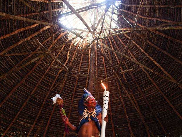 Dessana indigenous shaman Raimundo Dessana holds the Olympic torch during a ritual at the Tupe Reservation in the outskirts of Manaus, Brazil on Monday.