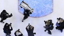 Los Angeles Kings' Jarret Stoll is pursued by photographers as he holds up the Stanley Cup after his team defeated the New Jersey Devils in Game 6 of the NHL Stanley Cup hockey final in Los Angeles, June 11, 2012 (Reuters)