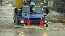 A Newfoundland Power truck drives through a flooded area of Waterford Bridge Road as it responds to calls during Hurricane Igor in St. John's, N.L., on Tuesday, Sept. 21, 2010. (Keith Gosse/Keith Gosse/The Telegram/The Canadian Press)