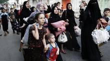 Palestinians flee their neighbourhood during heavy Israeli shelling in Gaza City on Sunday (FINBARR O'REILLY/REUTERS)
