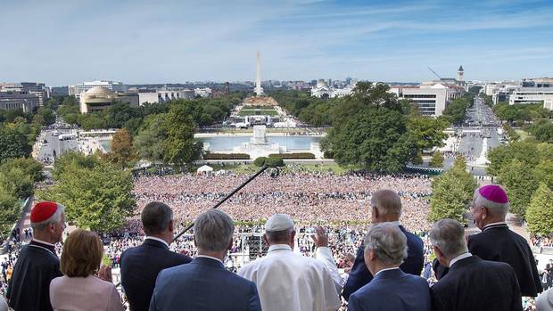 Pope Francis waves to the assembled crowd from the Speakers Balcony at the U.S. Capitol with members of Congress, Thursday, Sept. 24, 2015, in Washington after he addressed a joint meeting of Congress.
