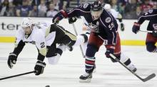 Columbus Blue Jackets' Mark Letestu, right, chases a loose puck as Pittsburgh Penguins' Matt Niskanen falls to the ice during the second period of Game 4 of a first-round NHL hockey playoff series on Wednesday, April 23, 2014. (Jay LaPrete/THE ASSOCIATED PRESS)