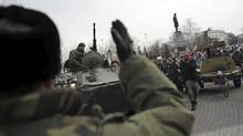 A Russian Army officer, back to camera, helps an armored personnel carrier drive on a street in Sevastopol, Ukraine's Black Sea Port that hosts a major Russian navy base, on Feb. 25, 2014 (ANDREW LUBIMOV/ASSOCIATED PRESS)
