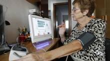 A heart patient monitors her blood pressure at home. (Albert Gea/Reuters)