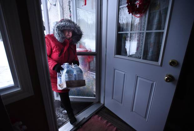 Serpent River First Nation Chief Elaine Johnston brings some bottled water to her parents' home on Dec. 20, 2016.