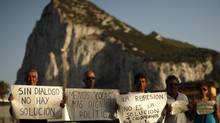 Spanish workers of the association of Spanish workers in Gibraltar (ASCTEG) and unemployed people pose for a photo as they hold signs in front of the Rock of the British territory of Gibraltar (rear), a monolithic limestone promontory, at the border in La Linea de la Concepcion, southern Spain August 6, 2013. (JON NAZCA/REUTERS)