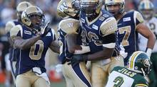 Winnipeg Blue Bombers' Johnny Sears (0), Demond Washington (15) and Alex Hall (96) celebrate a sack on Edmonton Eskimos' Steven Jyles (3) during the first half of their CFL game in Winnipeg on Thursday, July 26, 2012. (John Woods/THE CANADIAN PRESS)