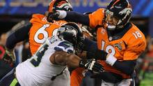 Denver Broncos quarterback Peyton Manning (18) passes before being tackled by defensive end Clinton McDonald (69) in the second half of the NFL Super Bowl XLVIII football game against the Seattle Seahawks at MetLife Stadium in East Rutherford, N.J., Feb. 2, 2014. (BARTON SILVERMAN/NYT)