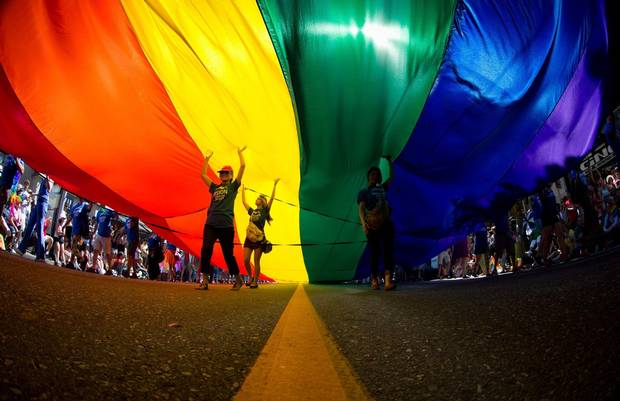 People carry an oversized rainbow flag down Robson Street during the Vancouver Pride Parade on Aug. 3, 2014.